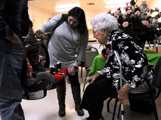 Crystal and Chase Canada show their 8-month-old daughter Clara to Ferne Lee  during a party to celebrate her 100th birthday at the Baird Community Center.