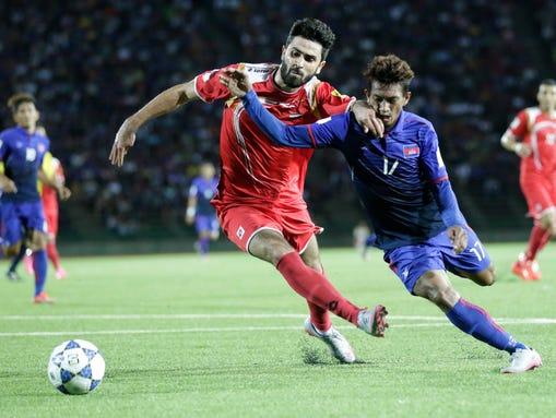 Syrian player Omar Kharbin  battles with Cambodian