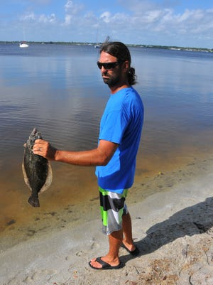 Alex Gorichky, a fishing charter captain and lagoon activist, holds a dead flounder during a fish die-off along the Indian River Lagoon in August 2016. The dead fish included flounder and rays lining the shallow water just offshore of the Pineda Causeway on the southeast side. Dead puffer fish and other species floated in the river or lined the shore.