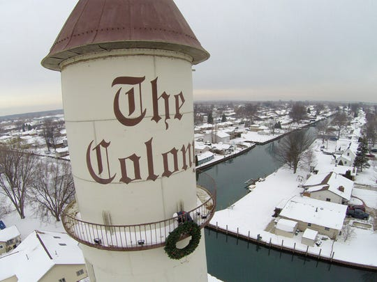 P.J. Harrison, of Phillips Sign & Lighting, works on changing the lights on the Colony Tower Wednesday, Dec. 21 in Clay Township. The current lights are too narrow and Harrison is replacing them with flood lights. Although the lights are not turned on while the Christmas lights are on but when the holiday season is over the lights will light up the top of the tower.