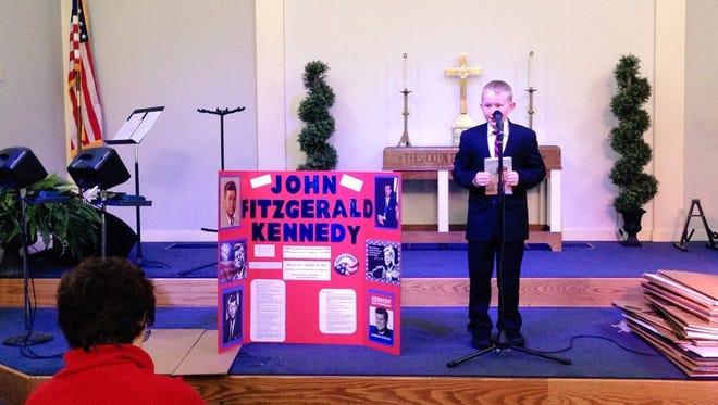 Grace Christian School fifth-grader John Skrobarcek gives his Biography Day presentation as John Fitzgerald Kennedy on Thursday.