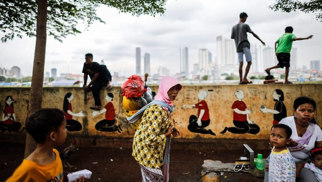 An Indonesian street vendor carries her belongings as others spend their time at a park in a slum area as high rise buildings are seen on the background in Jakarta, Indonesia, on Jan. 9, 2017.