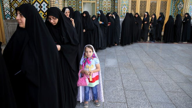 Iranian women line up to vote in the country's presidential election in the city of Qom, south of the capital Tehran, on May 19.