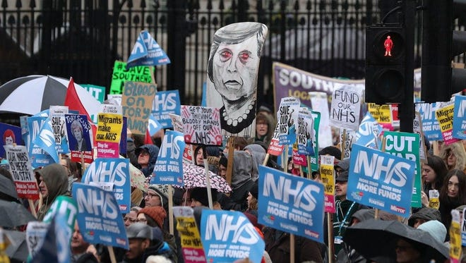 """A placard portraying Britain's Prime Minister Theresa May, center, is held by protesters during a march calling for an end to the """"crisis"""" in the state-run National Health Service (NHS), in central London on Feb. 3."""