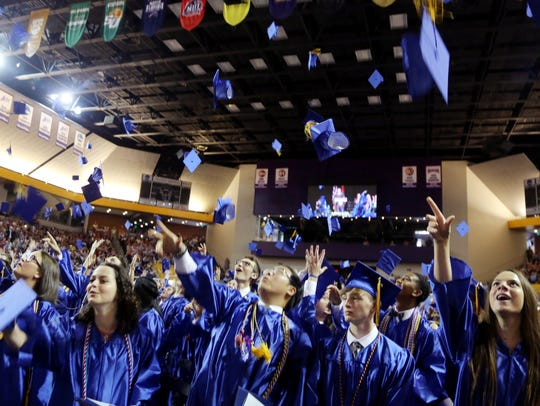 Graduates toss their caps during Brentwood High School's