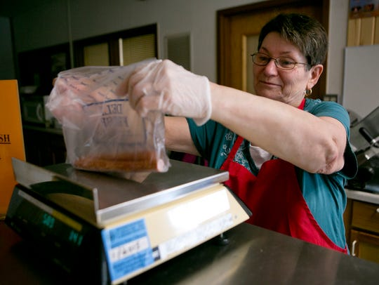 Owner Teresa Kulas weighs pork sticks for owner of
