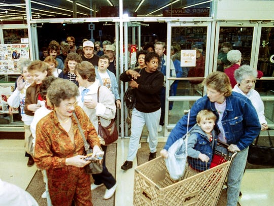 A large crowd of shoppers rush in the doors of Kmart