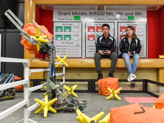 Grant Middle School's Phoenix Johnson (right) watches on as Surgeo Oswald controls the VEX robot the Grant Middle School robotics team took to VEX Worlds. The team demonstrated the robot's capabilities during an open house Tuesday.