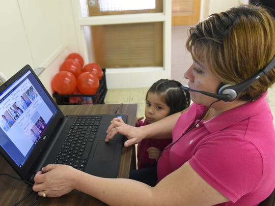 Janice CiFuentes uses a computer to study English at King Street Community Center, Chambersburg, Wednesday, May 3, 2017. Her daughter Giovanna Aujon watches.