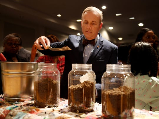 Union University President Dr. Samuel Oliver pours lynching site soil into one of the jars for one of the three lynching victims of Madison County during a memorial for Eliza Woods, John Brown, and Frank Ballard, Friday, Feb. 23, at Jackson State Community College.