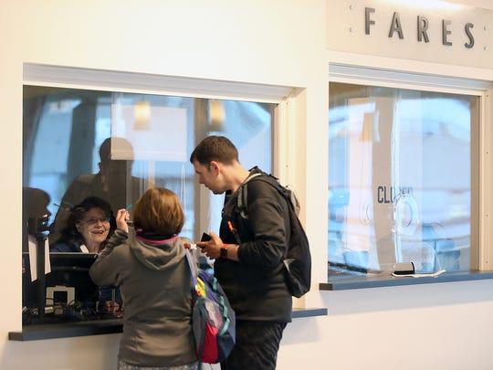 Ticket seller Lee Hewitt helps customers in the new ticket booth at Colman Dock in Seattle on Tuesday.