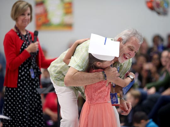 Armin Jahr Elementary School principal Mike Sellers hugs a kindergarten student during a graduation ceremony earlier this month. Sellers, who led the school through the accidental shooting of Amina Kocer-Bowman in 2012, is retiring this year after 43 years in education.