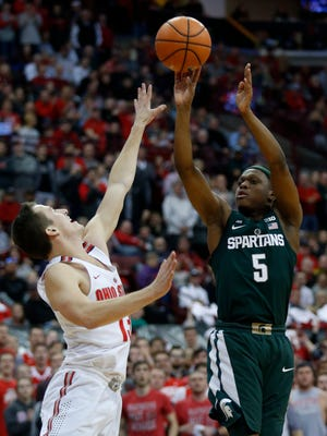 Michigan State guard Cassius Winston, right, goes up to shoot against Ohio State guard Andrew Dakich during the first half of MSU's 80-64 loss on Sunday, Jan. 7, 2018, in Columbus, Ohio.