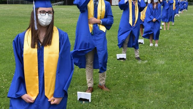 In a sign of the times, KHS graduate Isabel Allers wears a mask as she and her socially-distanced peers prepare to receive their diplomas on Sunday, June 7.