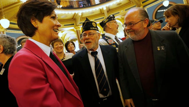Nick Lucy with the American Legion in Dubuque (center) and Veteran Joe Stutler of Marion greet Lt. Gov. Kim Reynolds Wednesday, Jan. 21, 2015, as she arrives in the rotunda for a program during Veterans Day at the Iowa State Capitol in Des Moines.