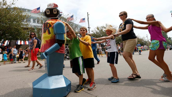 A line of people parade behind Oscar the robot Aug. 13, 2015, on the opening day of the Iowa State Fair in Des Moines.
