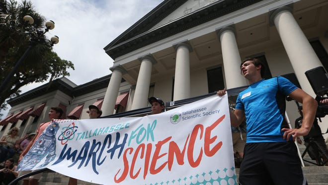 Greg Short, right, joins thousands of people gathering together at the Historic Capitol building downtown Saturday in a March for Science, part of a world-wide demonstration on Earth Day to promote the idea of scientific study and its relevance in society.