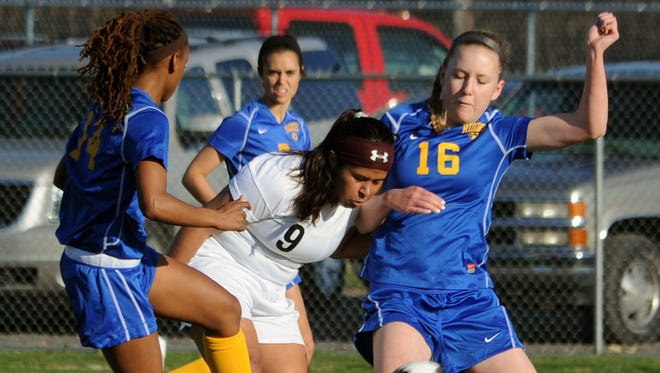 Sussex Tech's Wuendy Cruz (center) boots the ball away from Caesar Rodney's Janiah Moore (left) and Kristiana Stevens.