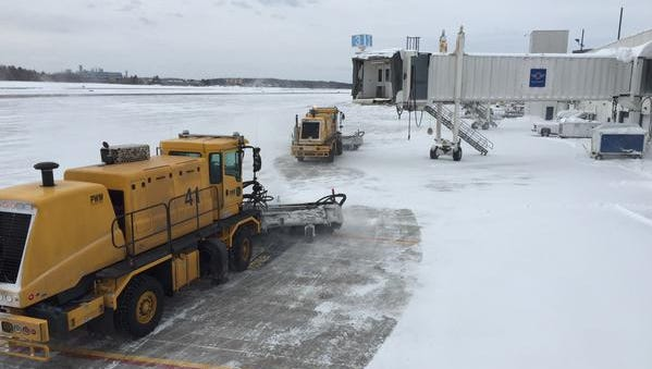 Plows work to clear the apron and taxiways at Maine's Portland International Jetport on the morning of Feb. 15, 2015.