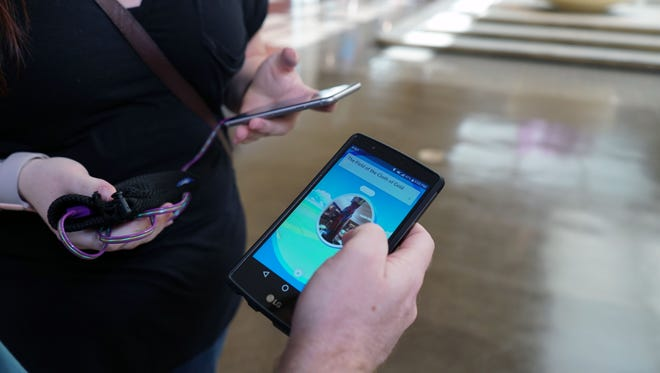 Matthew Pellegrini checks his phone while playing Pokemon Go at the NorthPark Center mall in Dallas as his friend Ashley Jenkins charges her phone with an external battery.