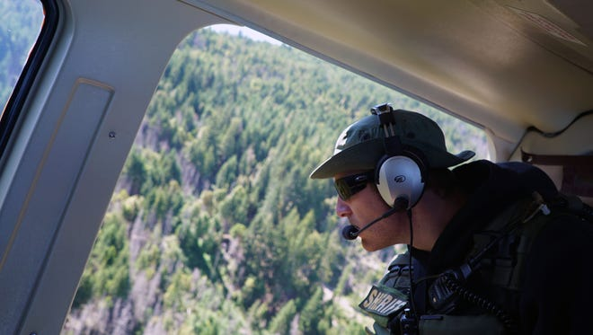 Deputy Kyle Holt of the Humboldt County Sheriff's Office leans out the open door of a helicopter flying over the county's mountain areas as he scouts for illegal marijuana grow operations.