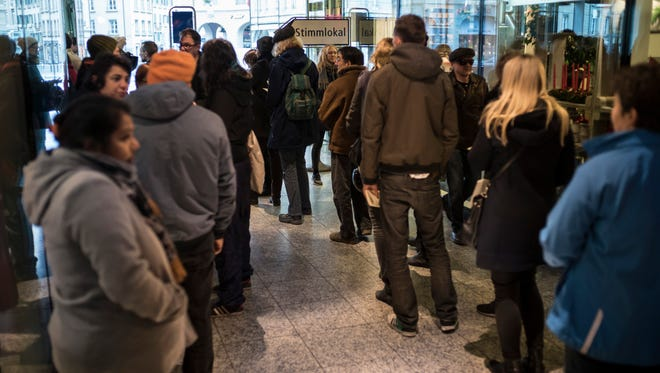 Swiss voters line up at a  voting center at the central railway station in Bern, Switzerland on Sunday.