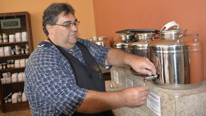 Rick Couron, co-owner of The Hearty Olive with his wife, Linda, pours a sample of dark chocolate balsamic vinegar. The new store is at 921 S. Eighth St., Manitowoc.