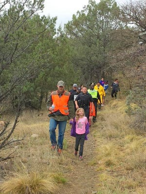 Officials walk down off a trail near Gomez Peak with the missing Harrison Schmidt Elementary students that were lost for a few hours on a field trip.