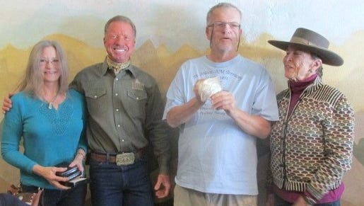 Members of the BLM Trail Blazers, from left, Jill Andrews, Matthew Midgett, and Caroline McCoy present a custom commemorative buckle to Mike Bilbo.