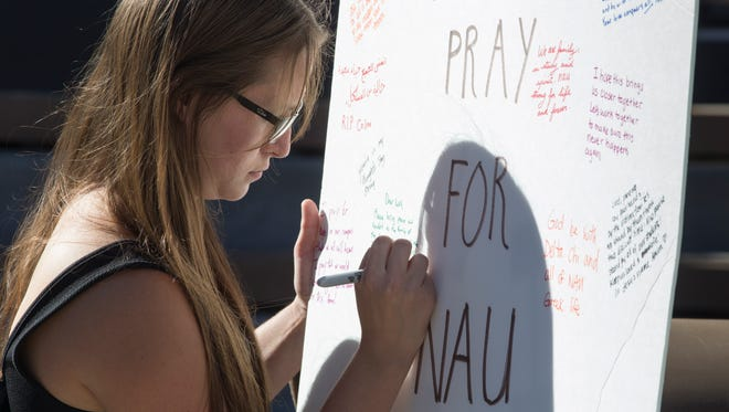 Melodie Prevost signs a card for the victims of Friday's shooting at Northern Arizona University, Oct. 9, 2015 in Flagstaff, Arizona.