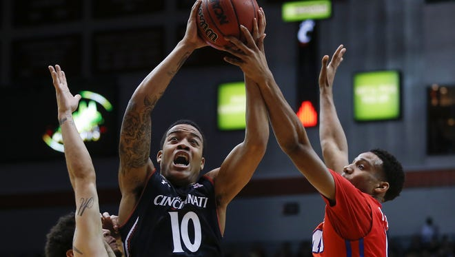 Cincinnati Bearcats guard Troy Caupain (10), center, is fouled on his way to the basket in the first half during the NCAA basketball game between the Southern Methodist Mustangs and the Cincinnati Bearcats, Sunday, March 6, 2016, at Fifth Third Arena in Cincinnati.