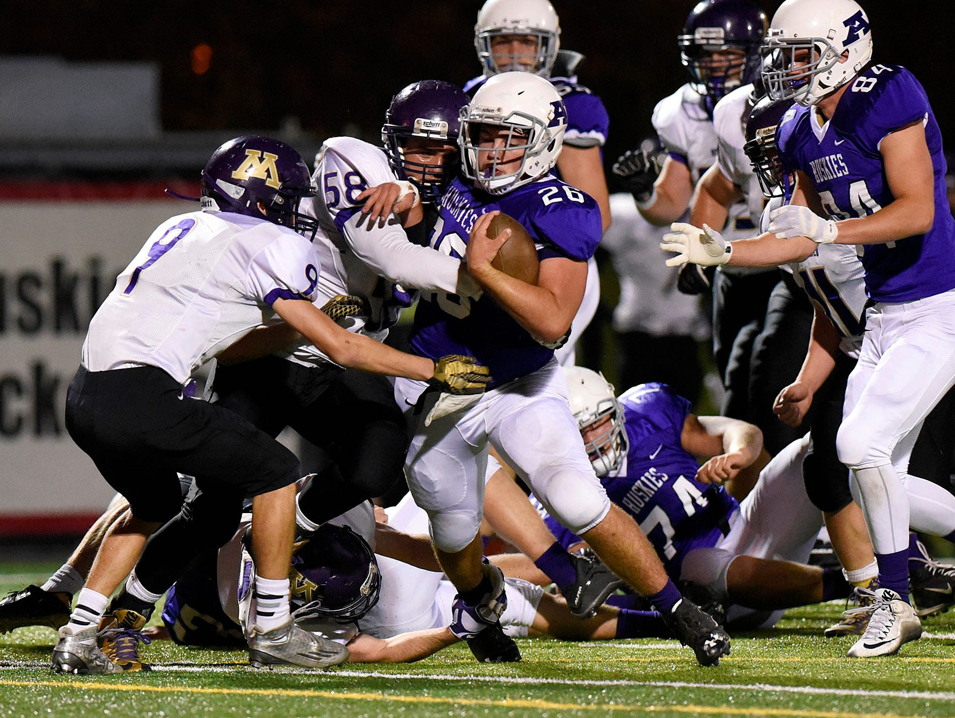 Albany's Will Kleinschmidt makes a short gain before being brought down by Montevideo's Preston Herfurth (9) and David Nelson (58) during the first half Saturday, Oct. 24 at Husky Stadium.