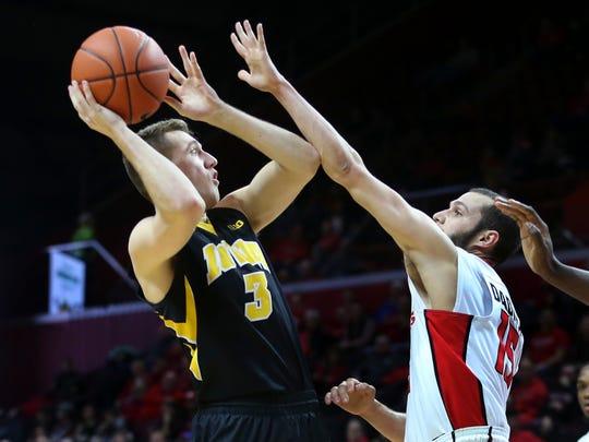 Iowa guard Jordan Bohannon (3) takes a shot past Rutgers guard Jake Dadika (15)
