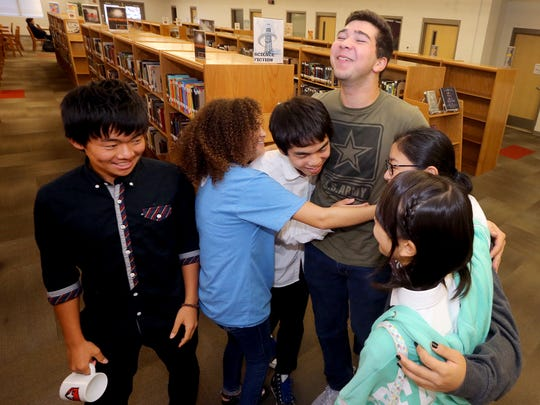 Matthew Parker (Center) is hugged by Japanese students