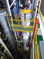 Employees involved with centrifuge testing early in the American Centrifuge Plant's run in Piketon look over one of the machines in this file photo. All of the centrifuge machines and other equipment have been moved out of the plant as cleanup work nears completion after the Department of Energy pulled funding for the centrifuge plant at the end of 2015.