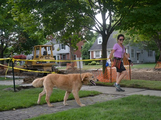 Jackie Benes walks with Buck along Villa Avenue where sewers are being stalled as part of the summer construction season in Birmingham.