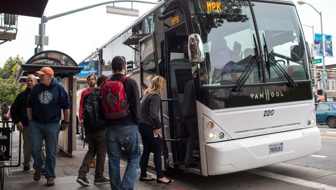 Software engineers, designers and IT employees of technology companies board shuttle buses to Silicon Valley April 14, 2014 in the Mission District of San Francisco, California. Approximately 35,000 employees use shuttle buses each day to be dropped off at Google, Facebook, Yahoo and Genentech corporate headquarters in Silicon Valley.