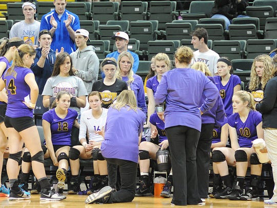 The Lexington volleyball team gets instructions from head coach Bobbi Weaver (kneeling) during the Division II state semifinal at Wright State's Nutter Center on Thursday.