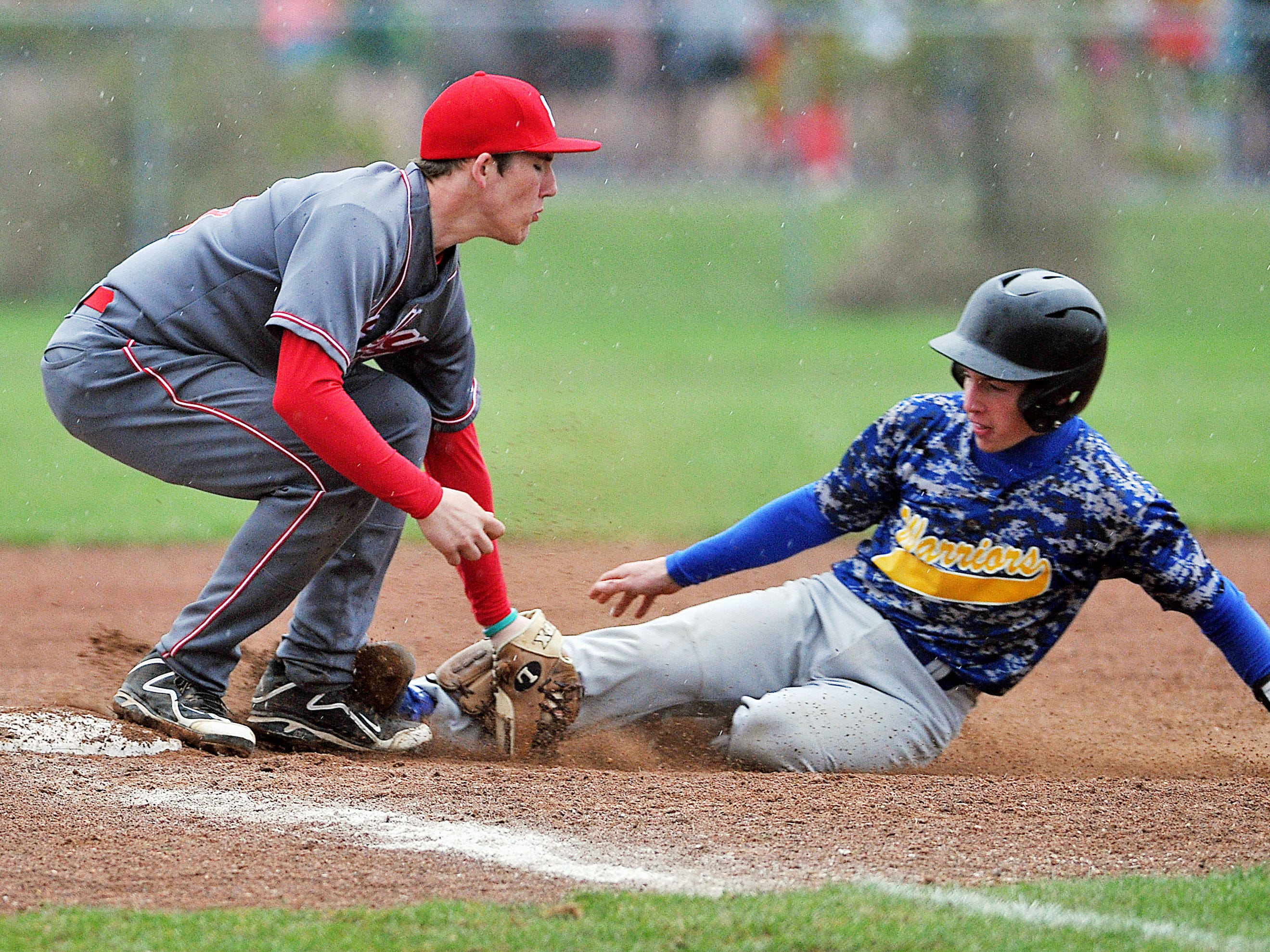 Shelby's Brennan Armstrong blocks the base as Ontario's Taylor Komives attempts a slide during a game Monday at Shelby. Komives was allowed the base.