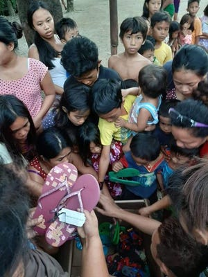 Daniel Matea of Alliance is founding director of Heart & Soles, a lay ministry which donates new shoes to needy families here and abroad. Here, kids in the Philippines receive new flip-flops.