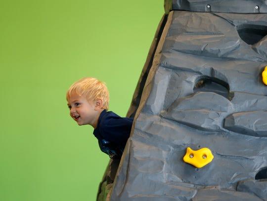Jayden Witt, 3, sticks his head out of a climbing wall