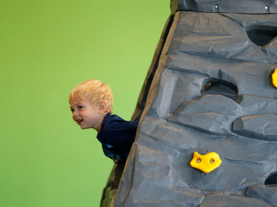 Jayden Witt, 3, sticks his head out of a climbing wall as he plays at the Jungle Gym, an indoor 'sensory play' environment for kids on Monday, July 16, 2018.