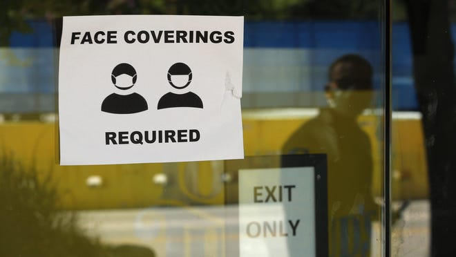 A man wearing mask to protect against the spread of COVID-19 is reflected next to a sign requiring face coverings at a business in San Antonio on June 24.