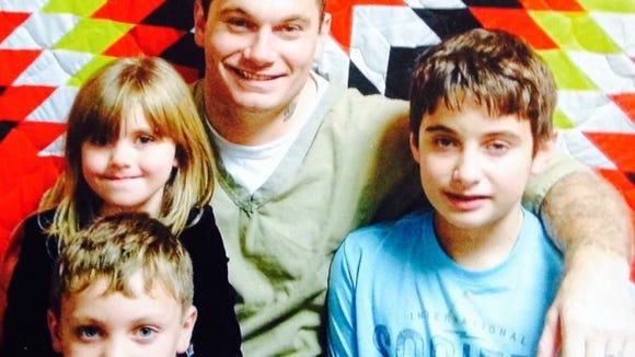 Chris Chipps poses with his three children at a powwow