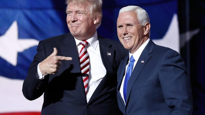 Republican presidential nominee Donald Trump (left) points toward his VP pick, Indiana Gov. Mike Pence, after Pence's acceptance speech at Republican National Convention in Cleveland last month. New Jersey Gov. Chris Christie was also under consideration for the No. 2 slot. A Monmouth University poll shows Trump getting a boost from Pence in Indiana, where he's up 11 points over Hillary Clinton. (AP Photo/Mary Altaffer)