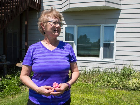Patti Guthrie stands outside her home located on the