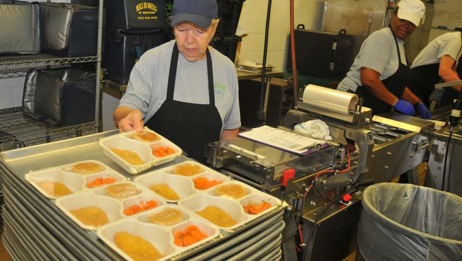Bonnie Spillman loads up trays with lunches for Meals on Wheels at the Brevard Community Kitchen in Cocoa, where meals are prepared daily for the volunteer-driven meals service and Seniors at Lunch sites.