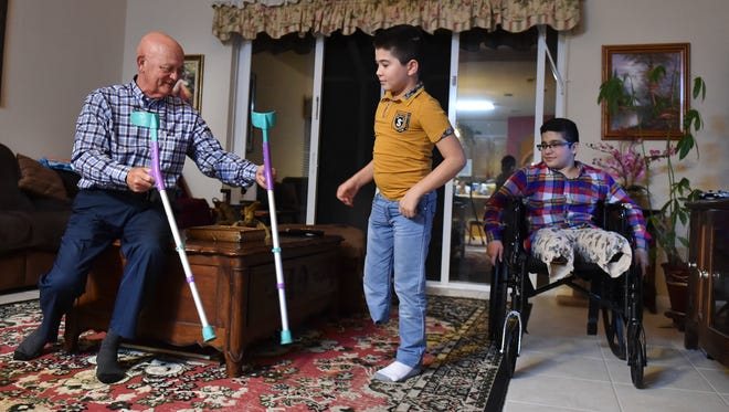 Mark Scott (from left) helps care for Doni Musaev, 13, and Abdul Saidov, 13, at Scott's home Dec. 14, 2017, in Vero Beach. Scott's relative Abdul, and Abdul's best friend, Doni, are recuperating after being hit by a car in February in their native country of Uzbekistan. The boys are undergoing physical therapy with the help of the Shriners Hospital for Children in Tampa.