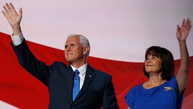 GOP vice presidential nominee Mike Pence waves to the crowd with his wife Karen after his speech.