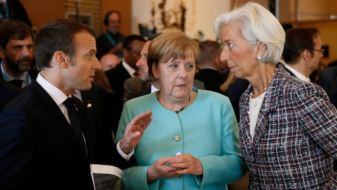 French President Emmanuel Macron, left, speaks with German Chancellor Angela Merkel, center, and Managing Director of the International Monetary Fund Christine Lagarde, right, as they attend a round table meeting of G7 leaders and Outreach partners at the Hotel San Domenico during a G7 summit in Taormina, Italy, Saturday, May 27, 2017. Leaders of the G7 wrap up their meeting on Saturday with discussions focused on terrorism, climate and trade.